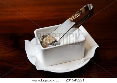 A Slice Of Sugar With Cinnamon And Tongs In A White Sugar Bowl Close-up On A Dark Wooden Background.