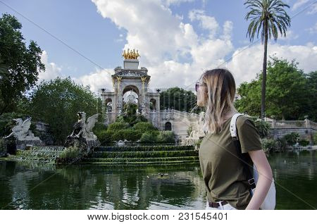 Amazing Young Wonam In Greed T-shirt And White Bag Looking On Fountain Of Parc De La Ciutadella, In