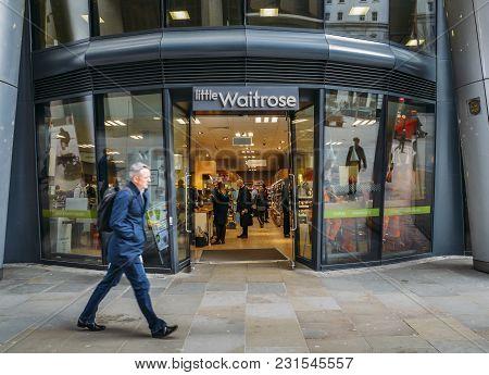 London, Uk- Mar 13, 2018: Officer Worker Walks Past A Little Waitrose Upmarket Supermarket In Walbro
