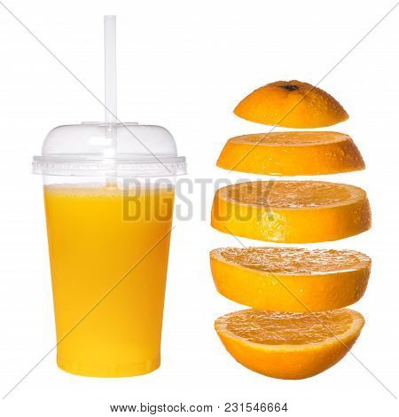 Fresh Orange Juice In A Transparent Glass With A Tube. Falling Sliced Orange On A White Background.