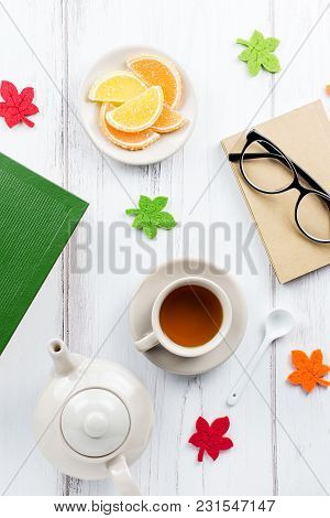Feminine Desk Workspace Flat Lay With Diary, Eyeglasses, Book, Tea Mug, Sweets And Felt Decor. Top V