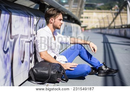 One Handsome Young Man In Urban Setting In European City, Sitting On The Ground