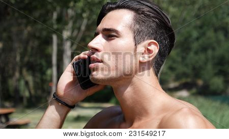Young Shirtless Muscular Handsome Man Making A Phone Call With Smartphone At Lake In Forest, Talking