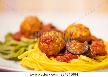 Two-colour Green And Yellow Italian Coocked Pasta With Meatballs, Tomatoes And Eggplant. Close-up Ph