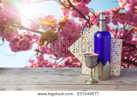 Passover Matzo And Wine On Wooden Vintage Table Over Spring Flowers Background.