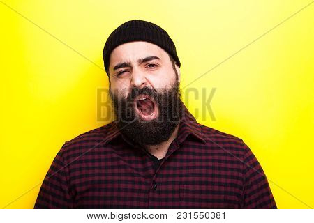 Yawning Hipster With Long Beard On Yellow Background