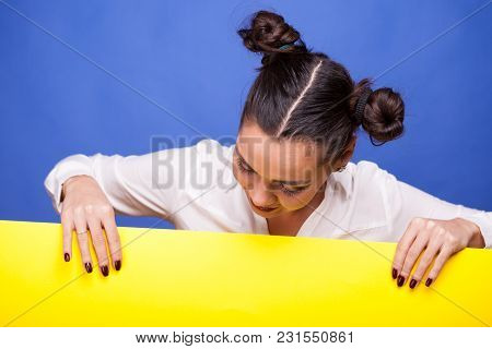 Woman Looking Down On Yellow Sign Over Blue Background In Studio Photo