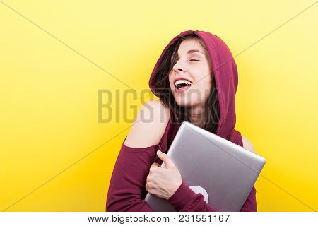 Smiling Student With Closed Eyes Holds A Laptop In Hands On Yellow Background In Studio