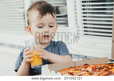 Baby In The Kitchen Drinking Orange Juice And Eating A Large Pizza
