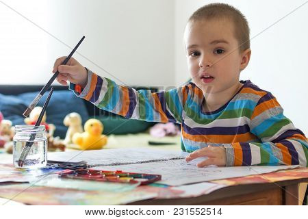 Cute Boy Sitting At Table And Painting With Brush