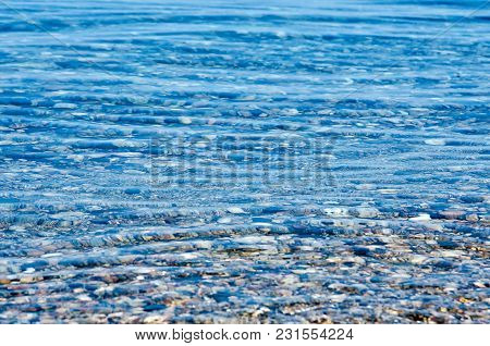 Beach With Pebble And Turquoise Water Under Blue Sky, Lake Baikal