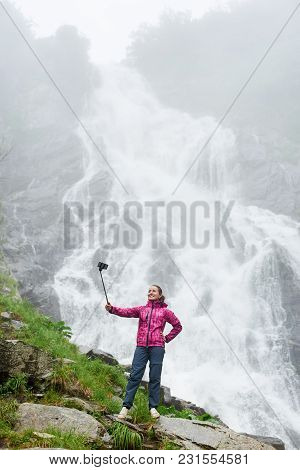 Girl In Trekking Clothing Standing On The Cliff And Taking Picture With Smartphone At Selfie Stick O