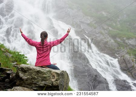 Back Of Pretty Young Woman Sitting On A Large Rock At The Big Powerful Waterfall. Beautiful Girl Enj