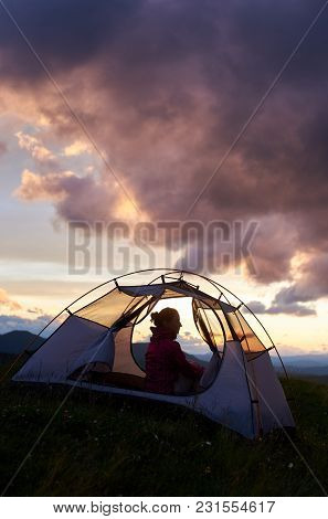 Silhouette Of A Girl Sitting In A Tent In The Mountains Of Romania And Enjoying The Sky At Sunset. A