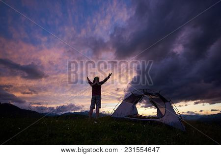 Woman Traveller Raising Her Arms Up Enjoys The View On Wonderful Dawn On The Mountain In Romania. Pl