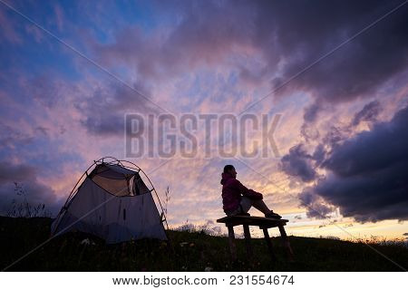Purple Sky. Young Female Tourist Enjoying Breathtaking Sunset Near Tent In Mountains In Romania. Clo