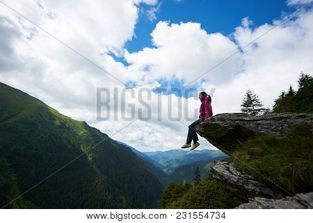Silhouette Of Young Female Tourist Sitting On The Rock, Dangling Her Legs In The Abyss Against The B