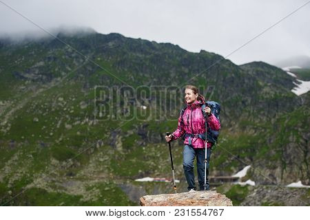 Young Hiker Woman Climbing Up In Green Rocky Mountains With Foggy Clouds. Smiling Girl In Pink Jacke