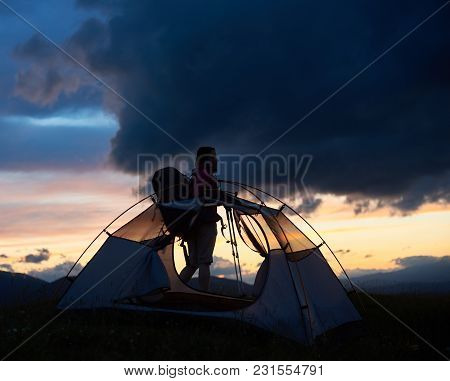Silhouette Of Young Female Tired Hiker With Trekking Sticks And A Backpack Near Tent, Sunset Time Wi