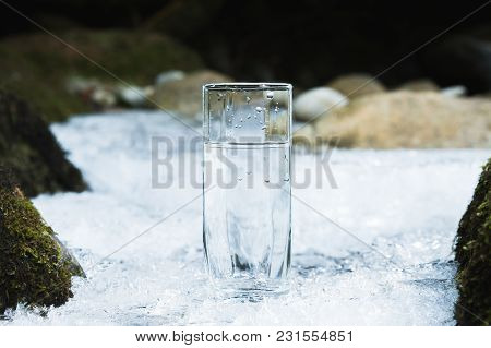 Transparent Glass Glass With Drinking Mountain Water In Winter Stands On An Icy Crust Against The Ba