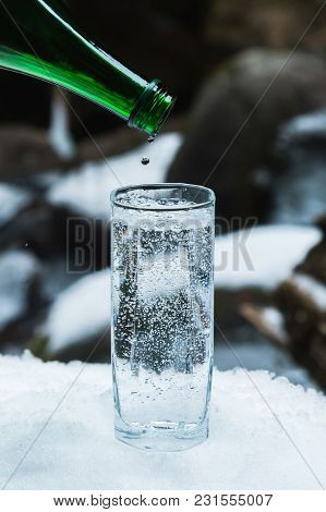 Pure Mineral Water Is Poured From A Glass Green Bottle Into A Clear Glass Beaker Until The Last Drop
