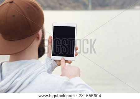 Close-up Of A Horde In A Brown Cap In The Open Air Holds A White Tablet Pc In His Hands. A Bearded M