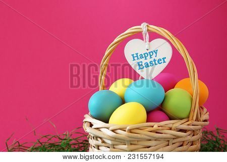 Colorful Easter Eggs Basket With Happy Easter Greeting Message On A White Wooden Heart.