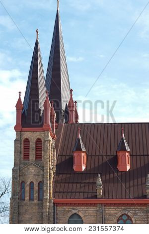 Twin Towers And Steeples Of Romanesque Revival Style Church Exterior And Roof Above Nave In Minneapo