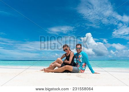 Romantic Couple Sit And Hug On Beach With Pure Transparent Water Of Ocean In Maldives