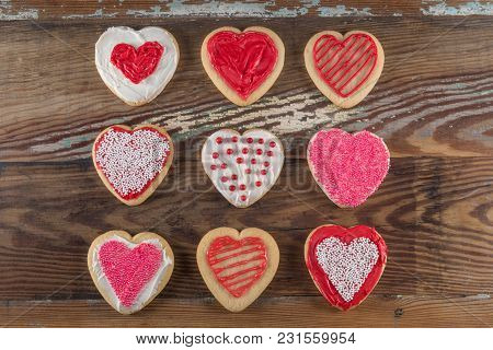 Grid Of Decorated Heart Cookies Over Wooden Table Top