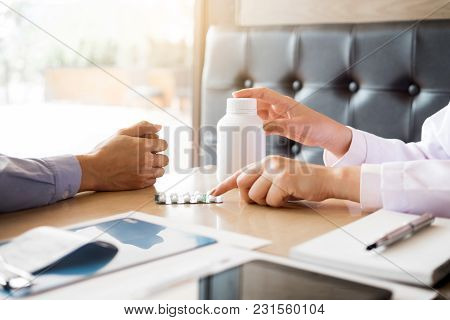 Doctor Hand Holding Tablet Of Drug And Explain To Patient In Hospital Room.