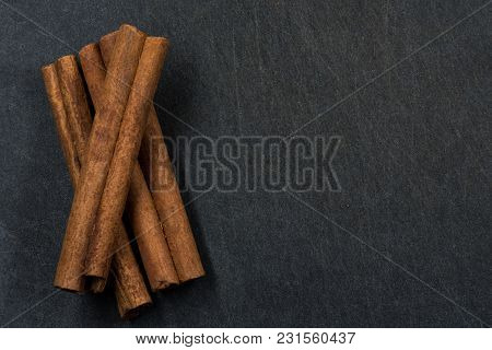Three Cinnamon Sticks On Black Slate Background With Copy Space To Right