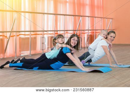 Parents And Children Go In For Sports. Young Mothers And Their Daughters Do Gymnastics And Do Yoga.