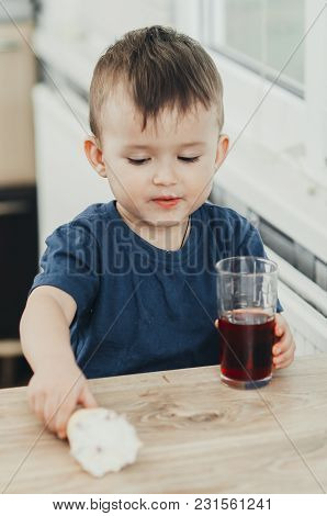 Charming Baby In The Kitchen In The Summer Drink Of Pomegranate Or Cherry Juice Red Color