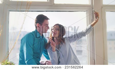 Young And Attractive Man And Woman Doing A Selfie Sitting At The Window, Love And Family Relations