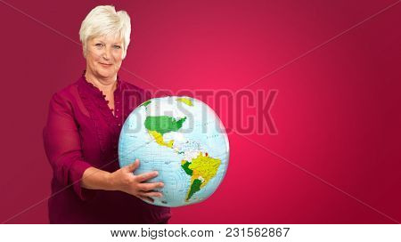 Senior Woman Holding Globe On Red Background