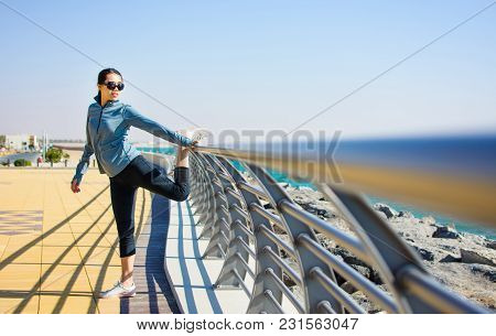 Girl Warming Up For A Workout By The Seaside. Active Lifestyle