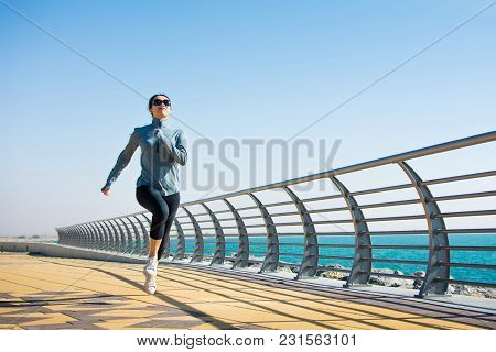 Girl Jogging On The Boardwalk For A Workout By The Sea