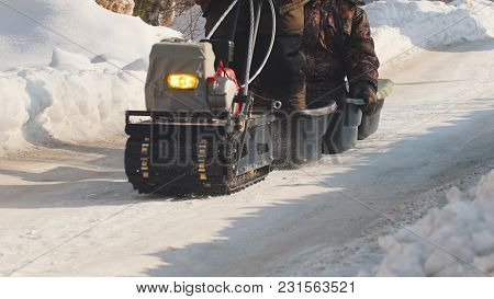 Man Riding On Crawler Mini Snowmobile With A Trailer And A Passenger On A Winter Road, Specialized V