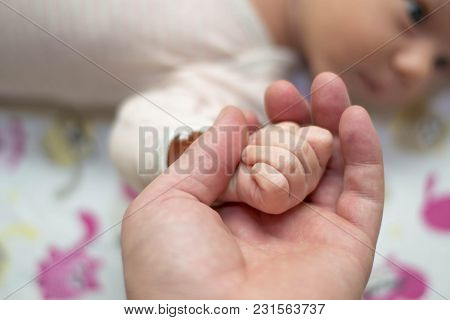 Dad Is Holding The Hand Of His Small Newborn Baby