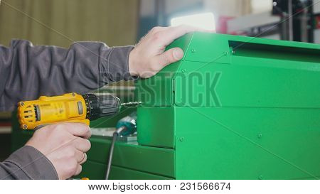 Worker Man Using An Electric Hand Drill - Making Hole In Green Metal Machine, Close Up