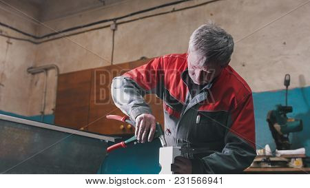Worker Assembling The Metal Part By Hand With Pliers, Tools For Grinding Metal And Metal Details In