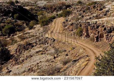 A Winding Dirt And Gravel Road Leads Through The Side Of A Deep Canyon In  Rugged And A Rocky And Ru