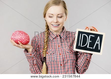 Young Woman Holding Idea Sign Banner On Black Board And Fake Brain. Studio Shot On Grey.