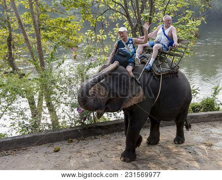 Kanchanaburi,thailand- February 20,2018: Tourists Ride Elephant By The River, To The Place Of Bathin