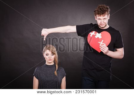 Broken Heart Difficult Love Concept. Sad Unhappy Couple Woman And Man Holding Paper Red Heart Fixed
