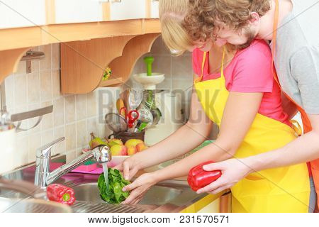 Young Couple Cooking Together, Washing Fresh Vegetables Red Pepper Green Lettuce In Kitchen Under Wa