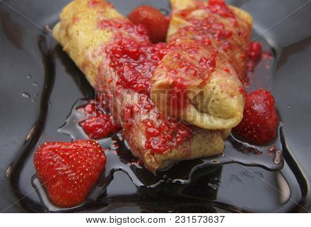 Rolled Up Pancakes Filled By Cottage Cheese And Strawberry Jam Over With Berries
