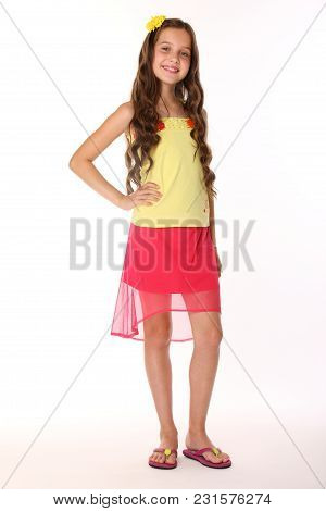 Pretty Brunette Slender Child With Chic Long Hair Is Stands Full-length In A Red Skirt With Bare Leg