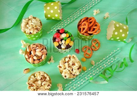 Popcorn, Multicoloured Drops, Pretzels With Salt And Pistachio Nuts In Paper Cups On Green Backgroun